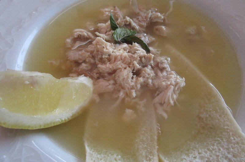 Sustancia de gallina, servida con sopas de pan y limón.